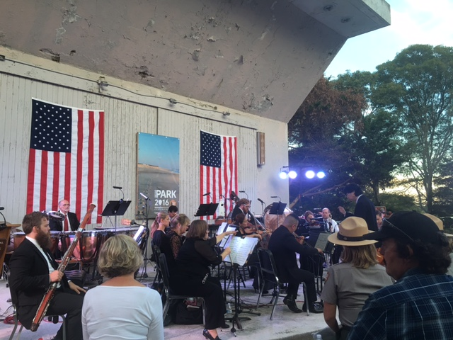A symphony plays in front of a large, white, concrete amphitheater in front of a large crowd on wooden benches. Two american flags hang on the wall behind the symphony.