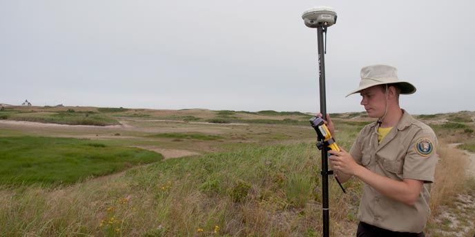 A science volunteer works with an RTK unit in the field at Cape Cod National Seashore