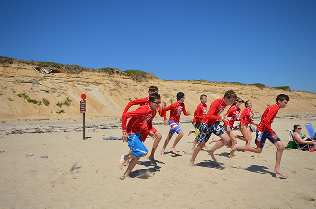 Kids in a variety of  colorful beach gear run down a beach on a sunny day with a cloudless sky.