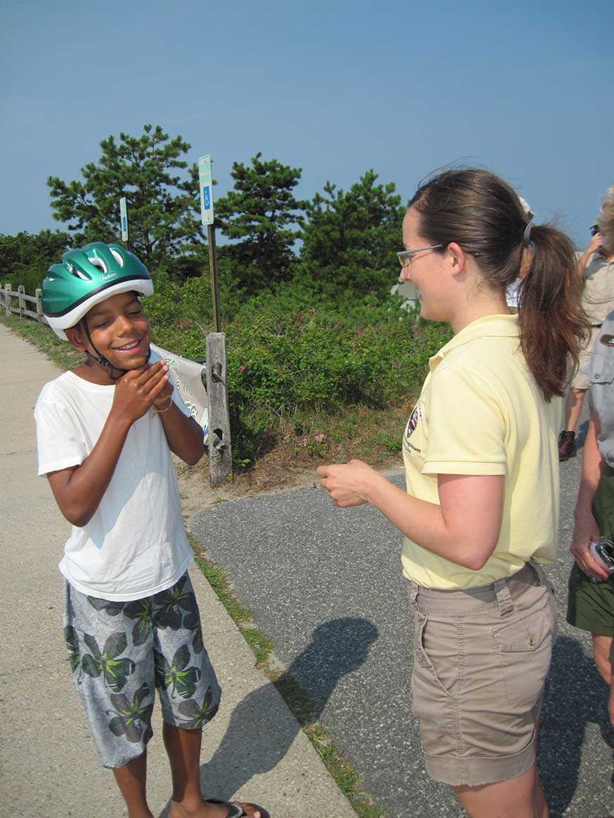 A National Park Service volunteer assists a young visitor in beach clothing with adjusting a bike helmet.