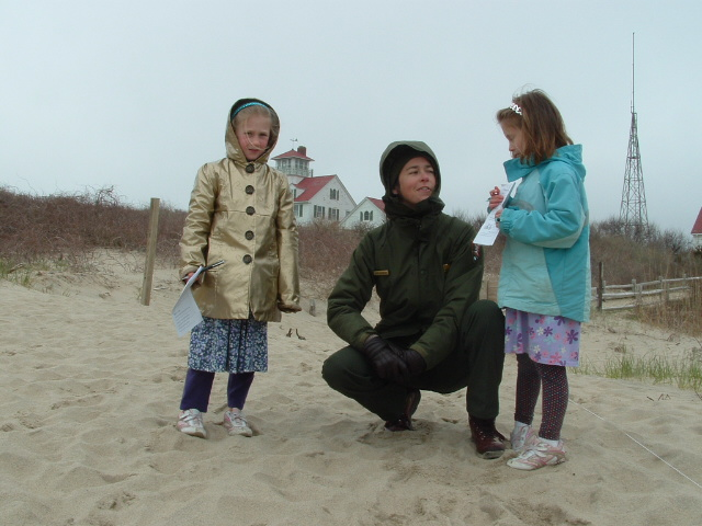 Two girls, age 8, stand on the sand with a ranger on a winter day, all bundled up in jackets and hoods.
