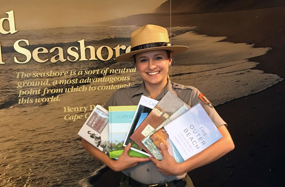 A ranger wearing a gray shirt and wearing a flat straw hat holds books fanned out in her arms.