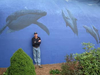 Large mural with blue water and black and white whales. Man stands in front of it.