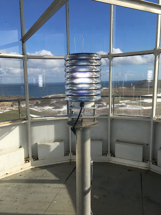 A blue LED light sits on a post inside the glass room of a lighthouse tower. Through the glass, a blue sky with light fluffy clouds can be seen.