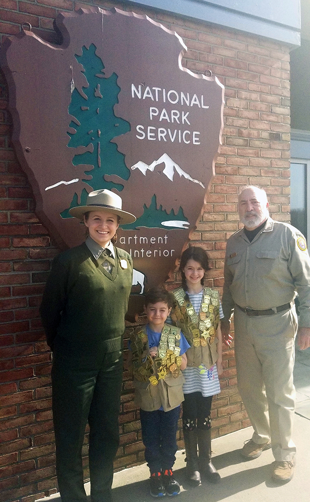A ranger, and a volunteer in a tan shirt stand on either side of two children wearing vests covered in plastic badges.