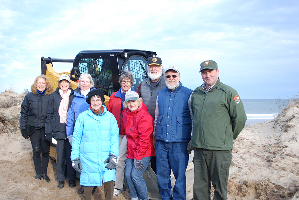 A group of people stand in front of a small yellow and black front end loader construction vehicle.