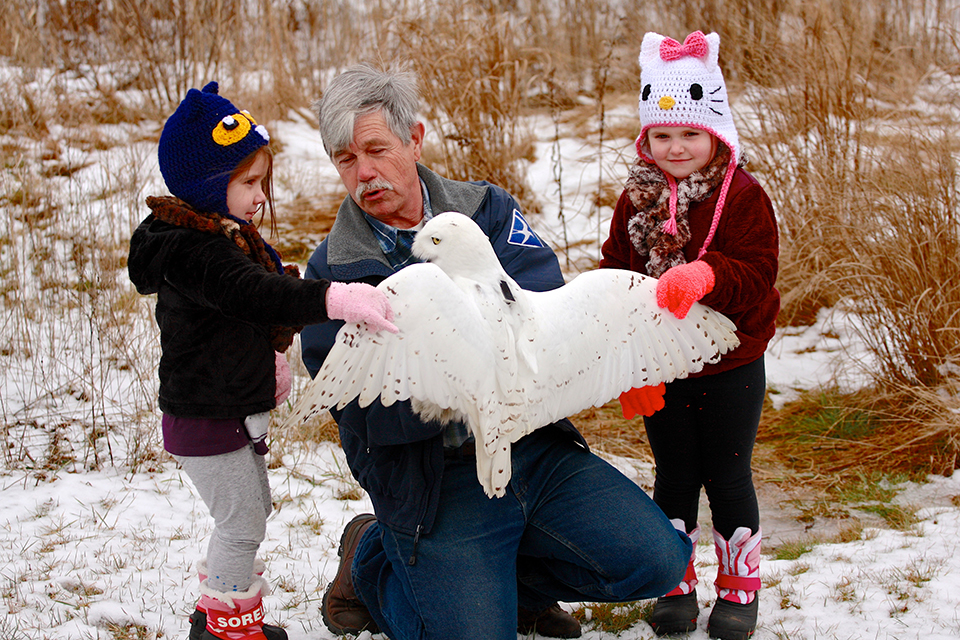 A man with gray hair and a mustache holds a large white owl with its wings spread as two children watch.