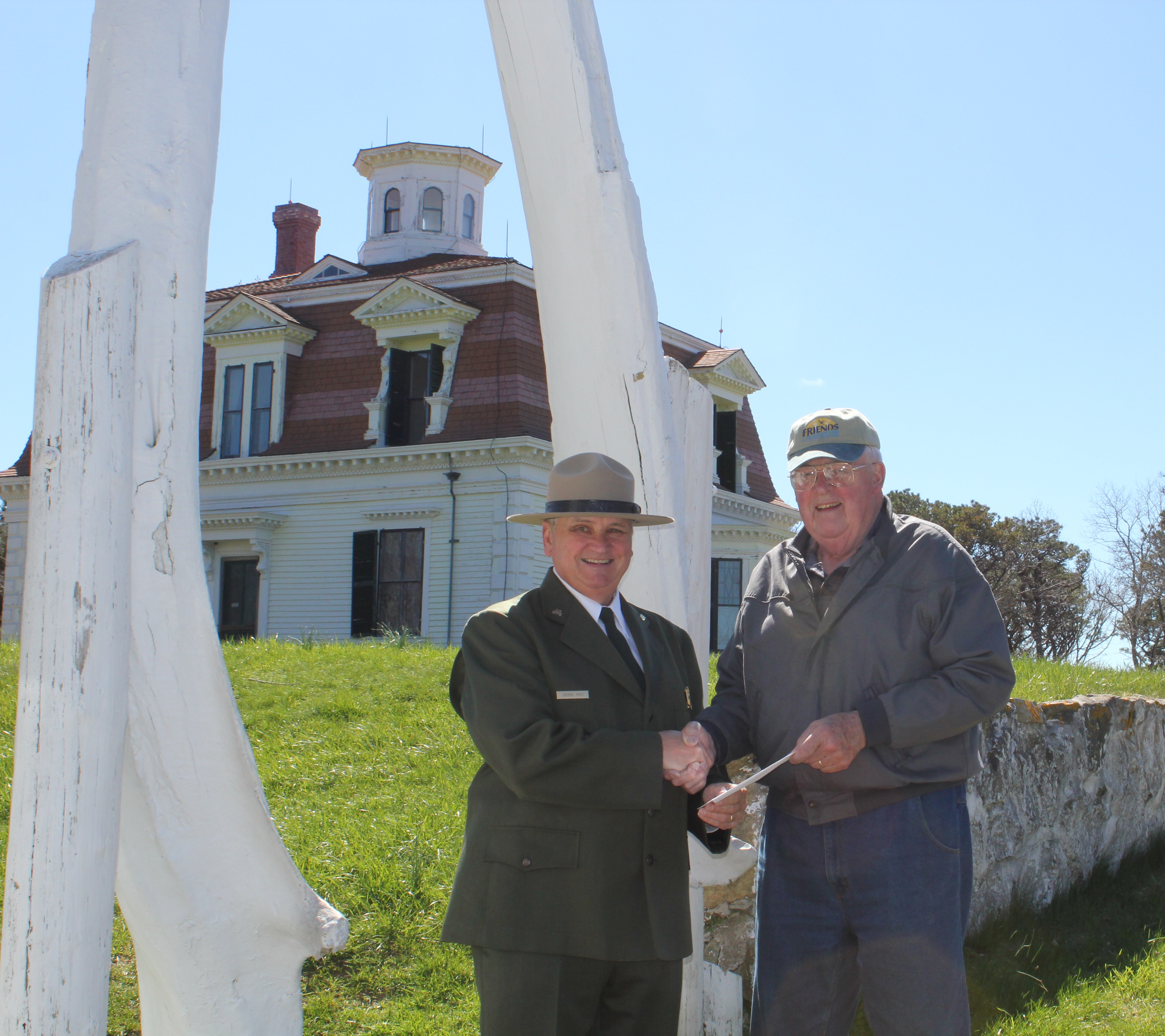 Richard G. Ryder, President of the Friends of Cape Cod National Seashore, hands Superintendent George Price a check for $100,000 as a partner match for the Centennial Challenge funding to repaint the Captain Edward Penniman House.