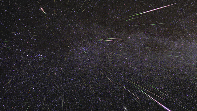 A field of stars and streaking meteors over the black darkness of space.