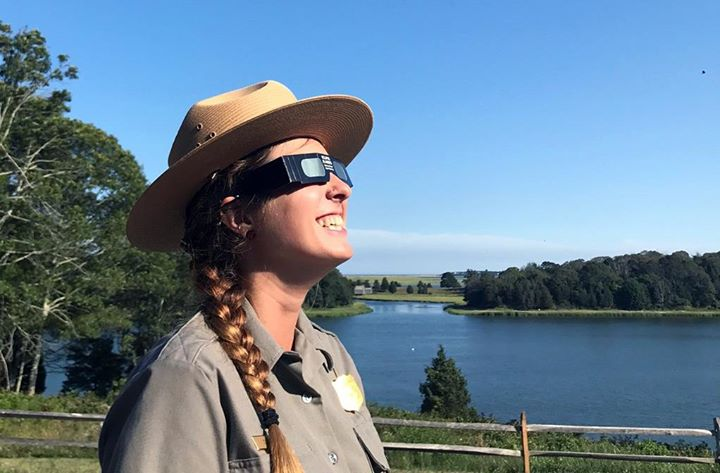 A ranger with long braided hair and a flat wide-brimmed straw hat wears cardboard sunglasses and looks up at the sky.