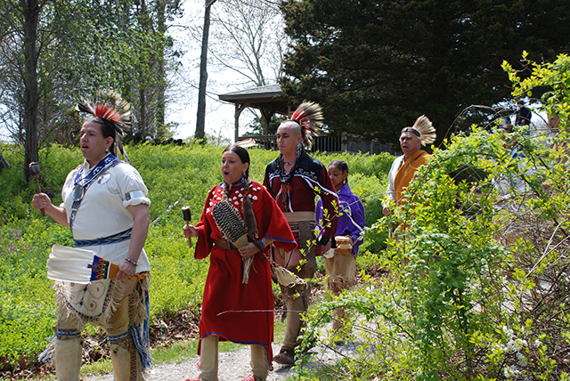 Native Americans in full dress walk down a concrete pathway from behind bushes, singing and chanting.