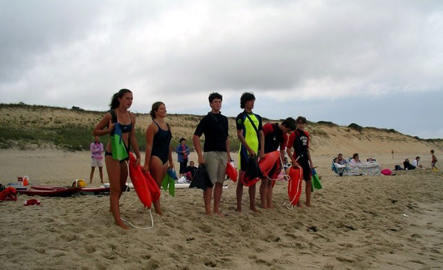 Junior lifeguards stand ready on an overcast day on a beach to practice their skills.
