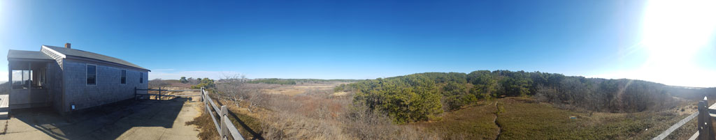 Panoramic photo of the outside of a wood shingle cottage looking over the ocean from a grassy hilltop.