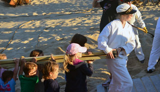 A young woman dressed as a surfman in white  carries a ladder with the help of many children.