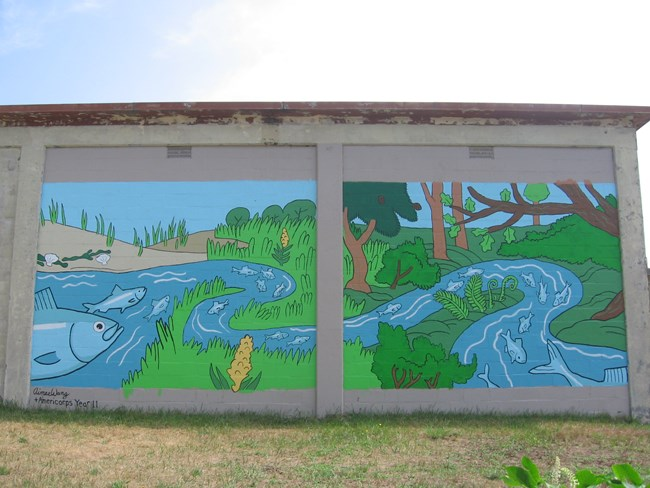 A brick wall covered with a colorful mural depicting grey fish swimming up a river.