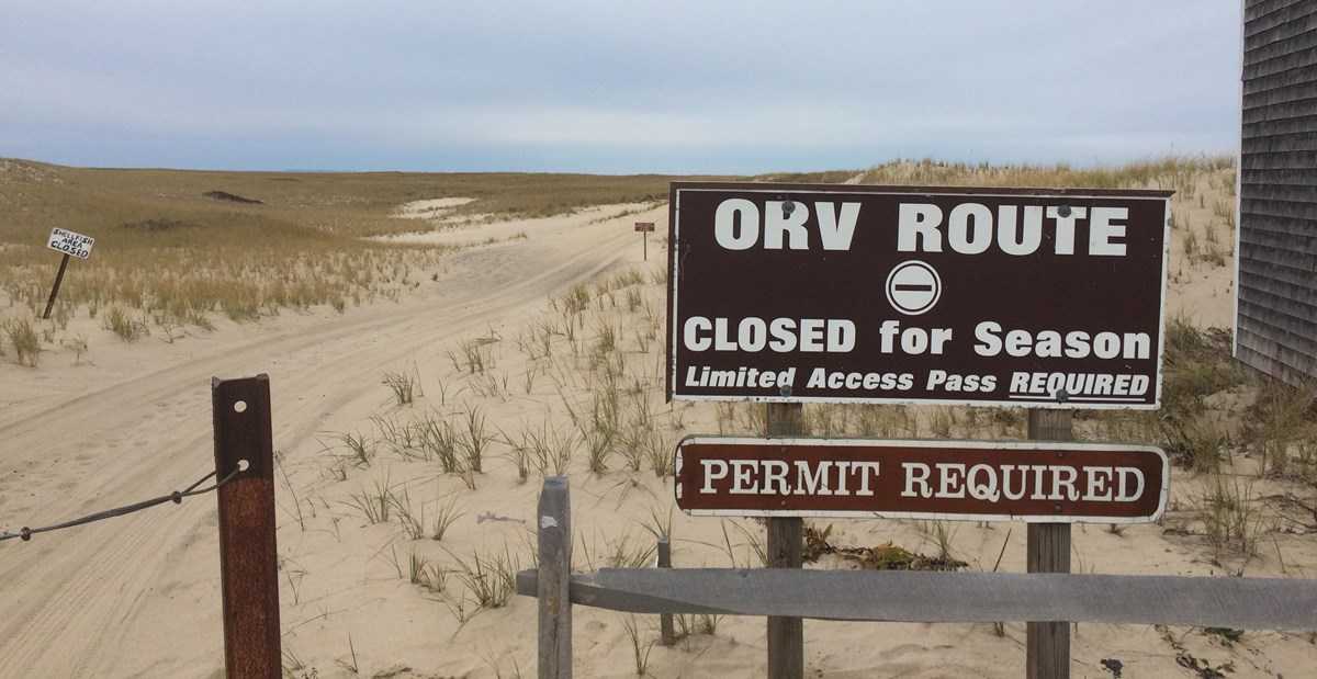 "A sign reads, ""ORV Route Closed for Season, Limited Access Pass Required"" against a sandy dune road that leads out to the ORV corridor."