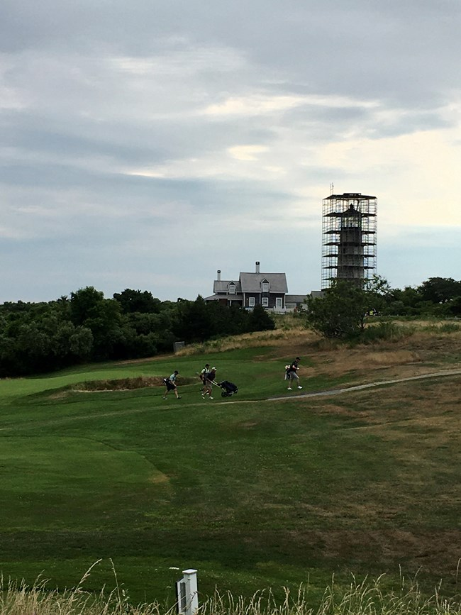 Golfers walk across a green golf course against the backdrop of a tall lighthouse with scaffolding around it.
