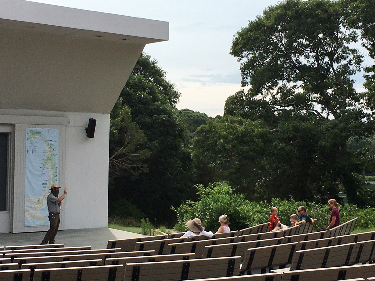 A ranger stands on a stage in front of a small group of visitors near a pond. There is a large park map hanging next to him.