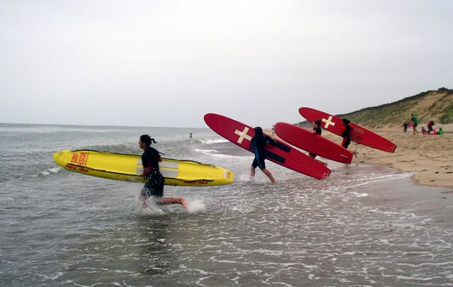 Junior Lifieguards run into the surf carrying long red and yellow surf boards.