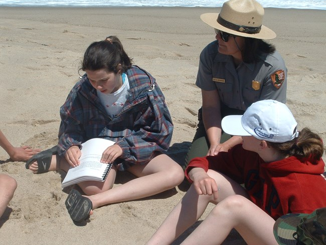 A young woman sitting on the beach reads a Braille lesson