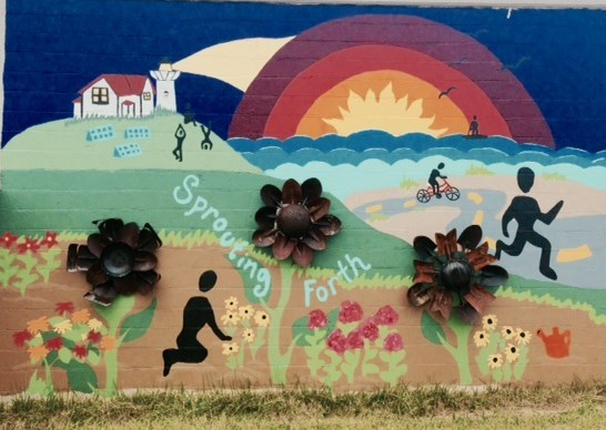 A brick wall with a colorful mural of black silhouettes engaged in a variety of activities on a hill by the ocean. There are four welded metal flowers as part of the mural.