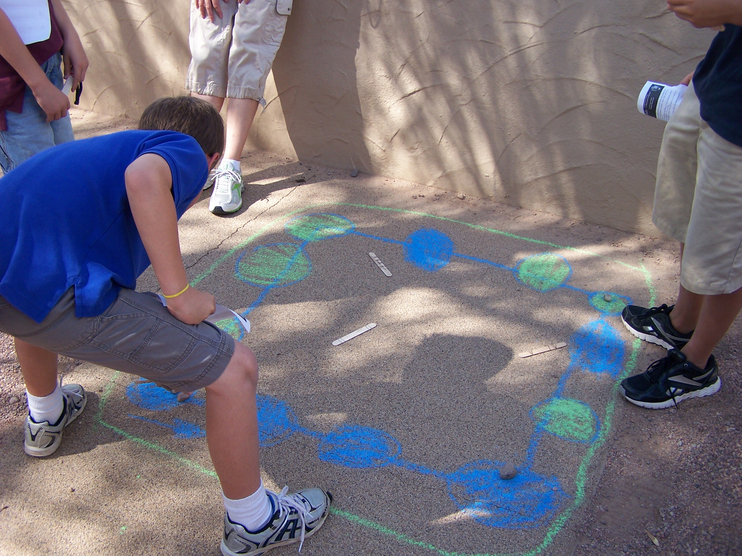 sidewalk chalk outlines the playing board for the 'stick game' students are learning