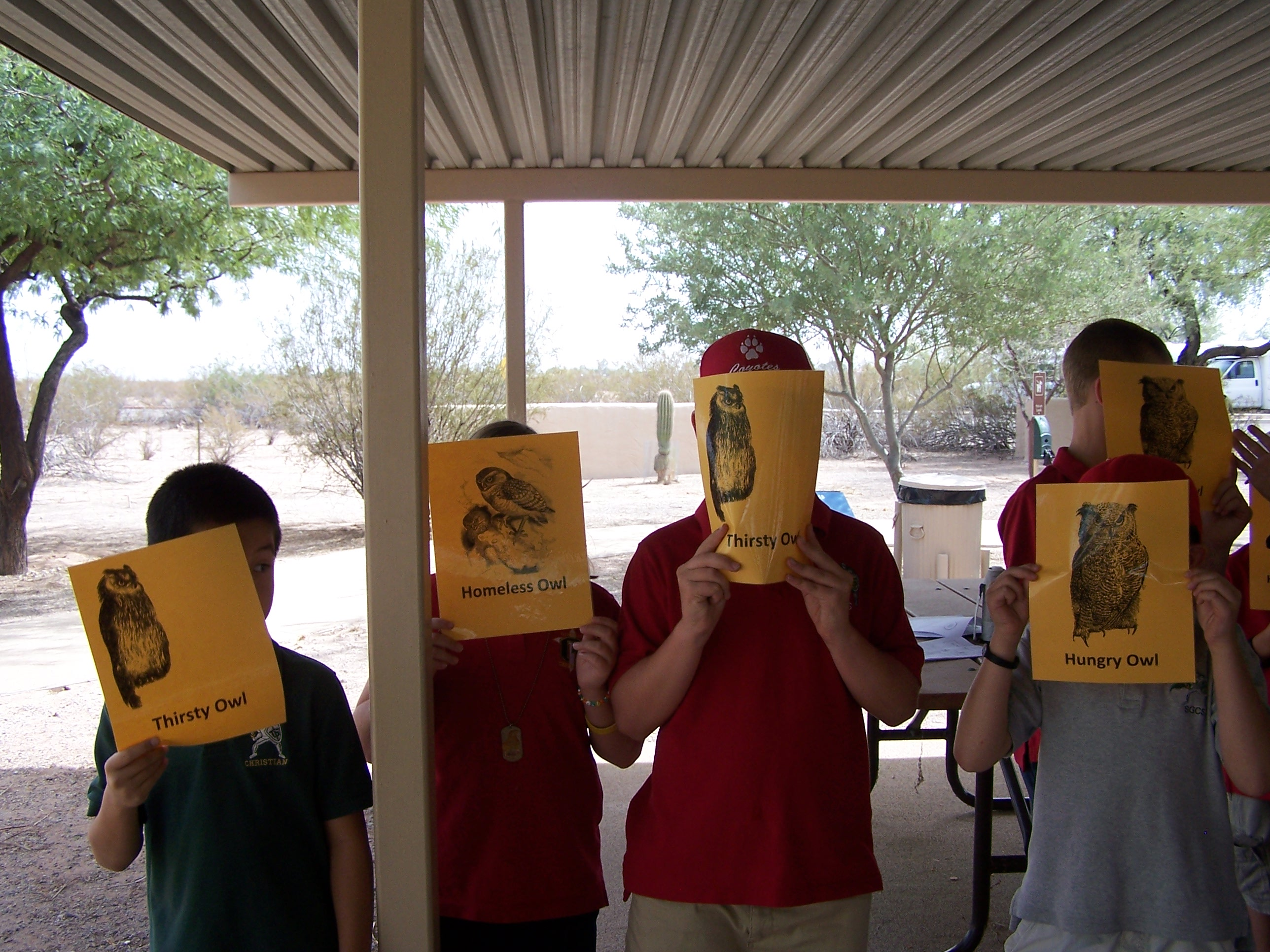 students cover their faces with gold cards explaining what resource they need (water, home, or food)