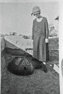 black and white image of woman in 1920s clothing looking at a large olla pottery artifact