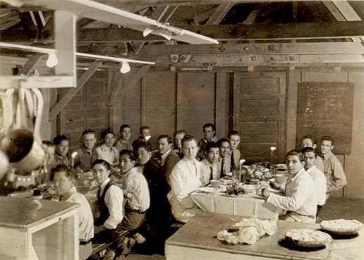 black and white photograph of men sittting at tables about to eat dinner
