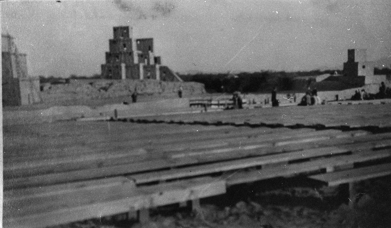 this black and white historic photograph shows the wooden plank seating facing a fake 'adobe' building on the earthern mound of compound b
