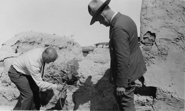 Black and white photographs from 1936 of man in dress pants and shirt spraying chemicals on ruins while uniformed ranger watches