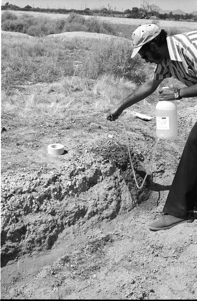 Black and white photograph from 1973 showing a man applying chemicals to the ruins using a spray tube