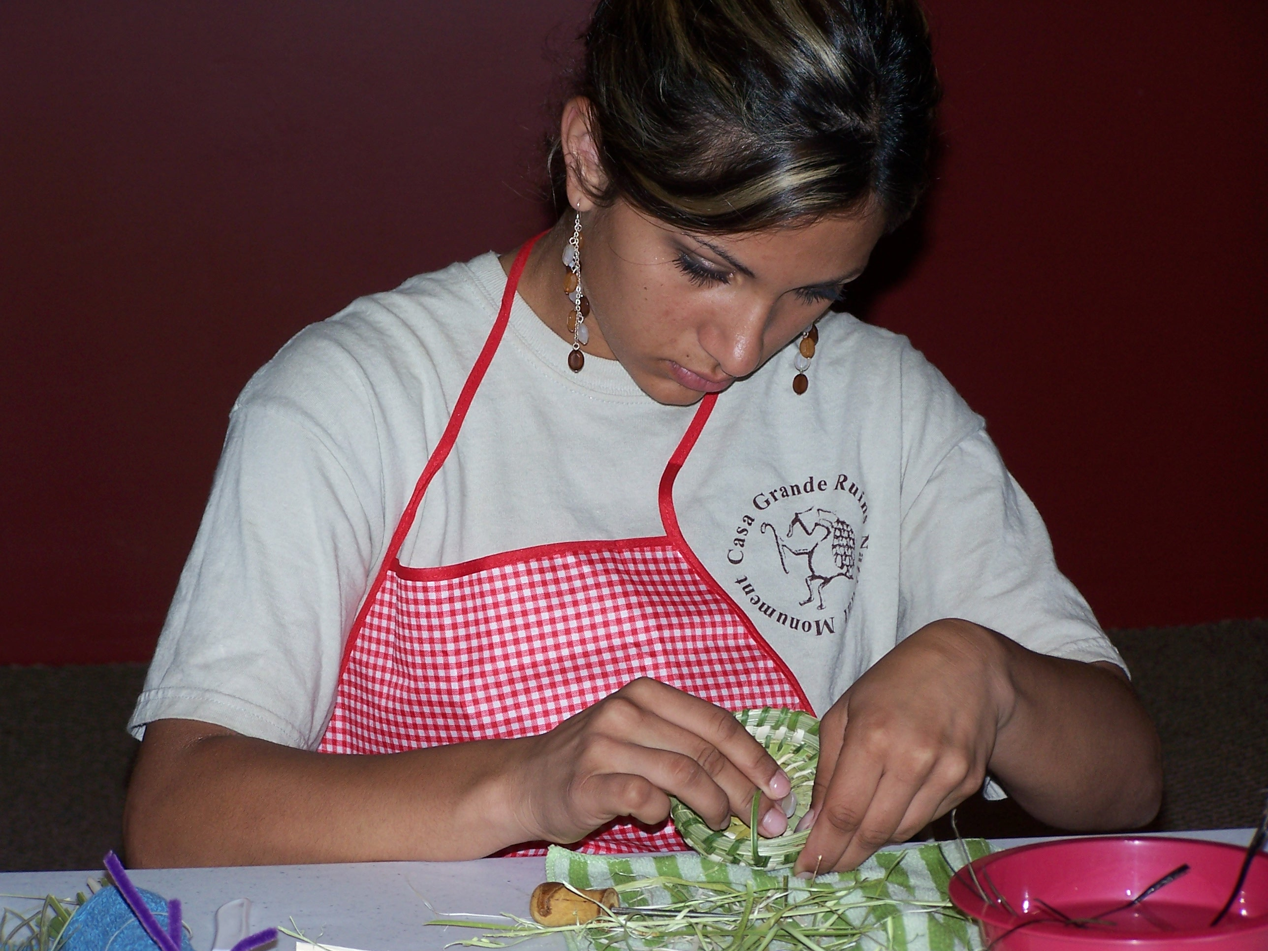 Sitting at a table with her work apron on YCC student works green yucca around the bear grass on the basket's edge