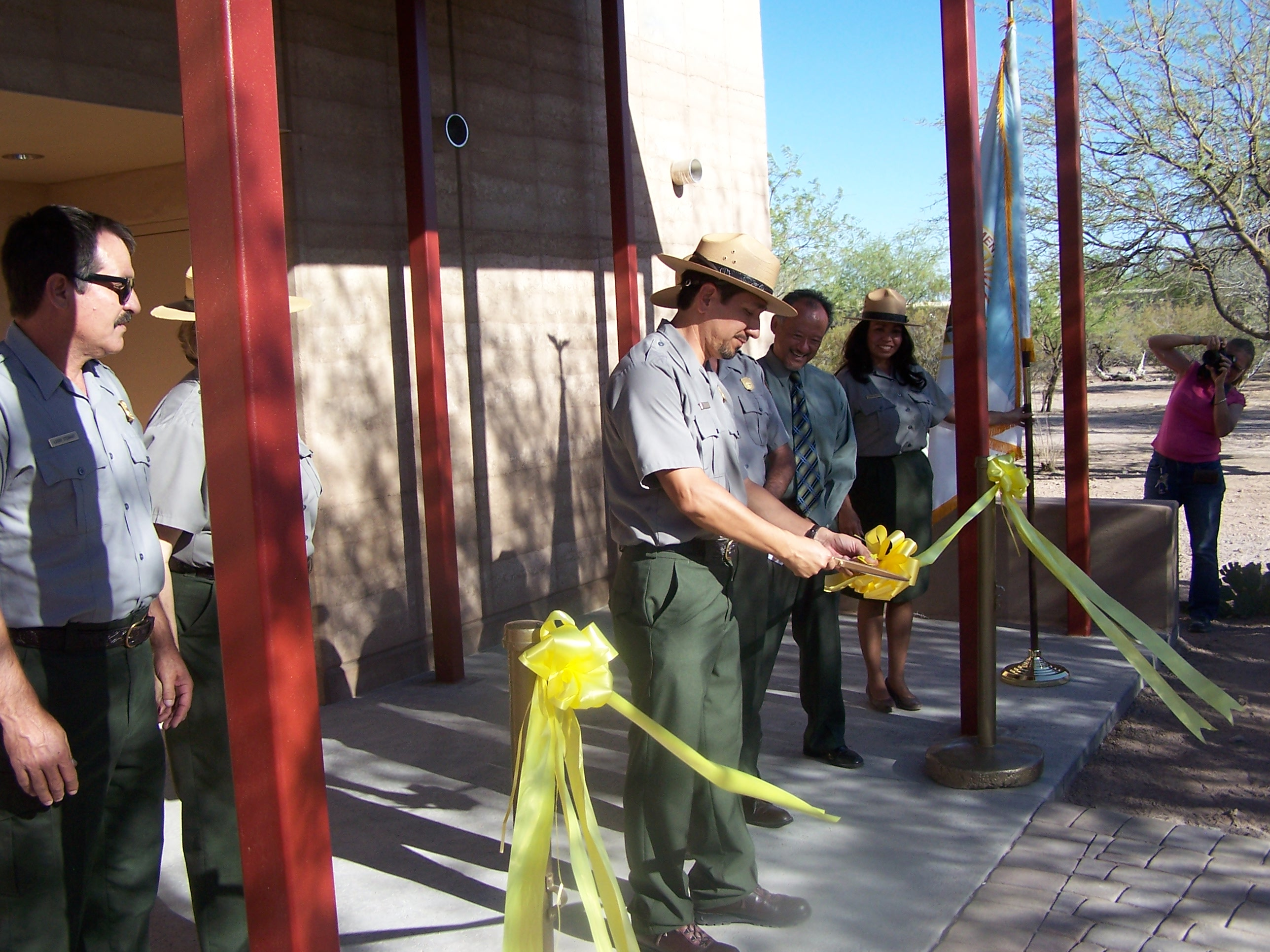 Superintendent Karl Cordova cuts yellow ribbon to open new visitor center addition