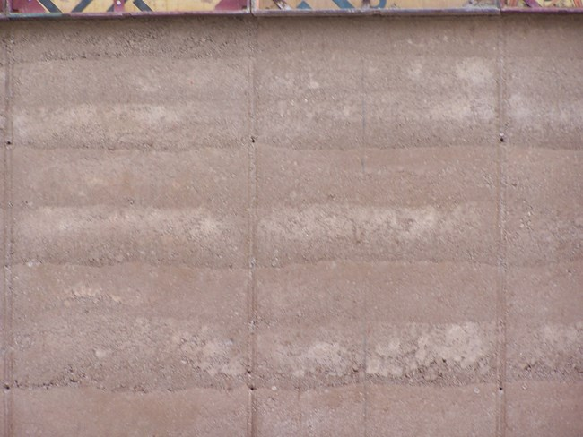 rammed earth wall close up shows layers in different shades of tan