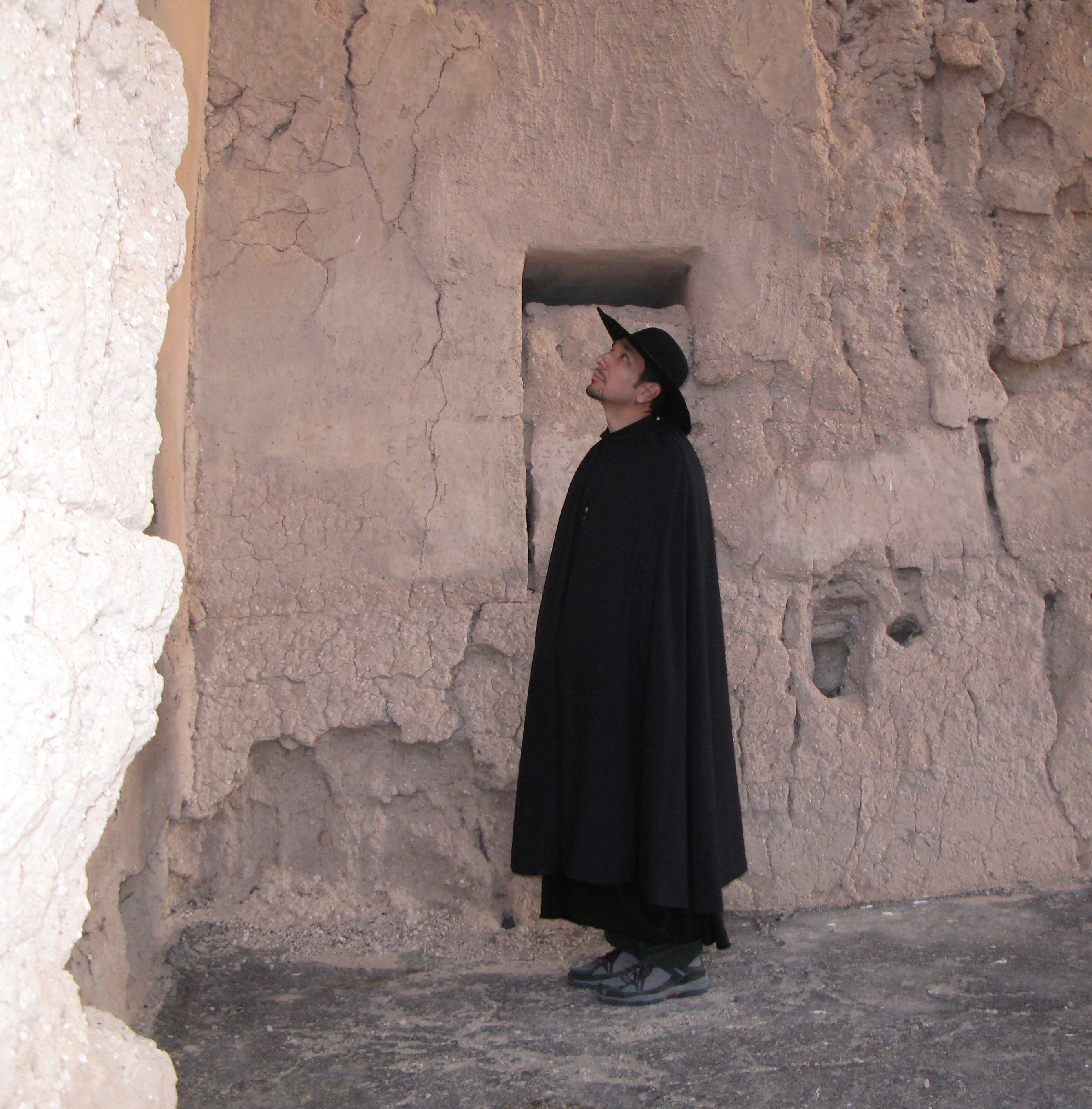 Park Superintendent dressed in dark historical robes  and a dark brimmed hat stands inside the Great House ruins as part of the film shoot