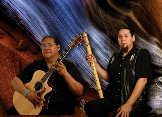 Aaron White andAnthony Wakemen pose in a studio with their guitar and flute