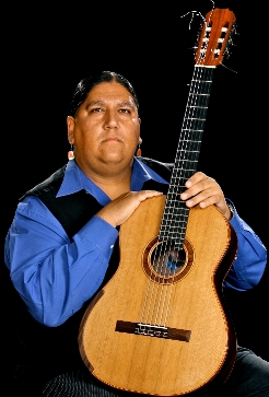 Gabriel Ayala sits with his guitar in this studio photograph