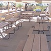 picnic area tables in the shelter that contains the outdoor kitchen