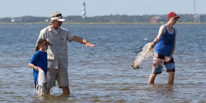 Volunteer and two visitors standing and cast-netting in the Pamlico Sound with the Cape Hatteras Lighthouse visible in the distance