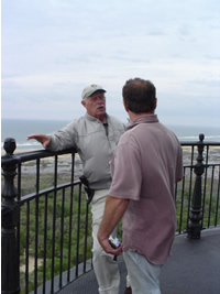 A volunteer greets a visitor on the gallery deck of the Cape Hatteras Lighthouse.