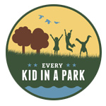 Every Kid in a Park logo of three kids playing in a field next to two brown trees.