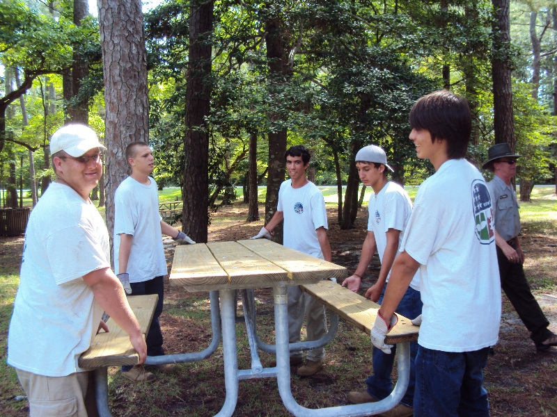 Members of the park's Youth Conservation Corps crew work on a picnic table.