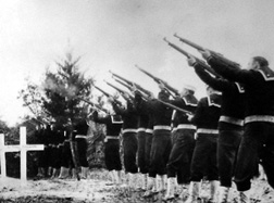 A 21-gun salute honors the British sailors at their burial in 1942.