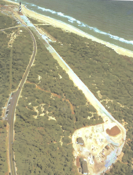 An aerial photograph shows the Cape Hatteras Lighthouse with a path cut through the trees to the lighthouse's new home.