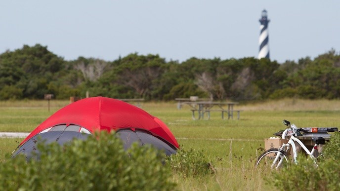 Tent with red cover at Cape Point Campground; Cape Hatteras Lighthouse in background
