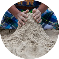 A child sculpts sand with two hands