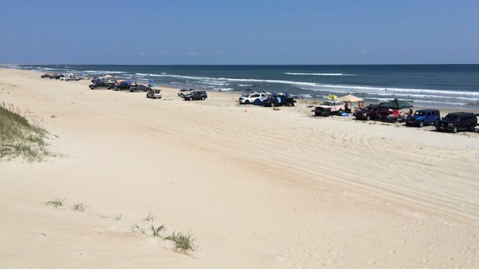 Visitors to the South Beach part of Cape Hatteras National Seashore with their off-road vehicles parked in a line along the beach.