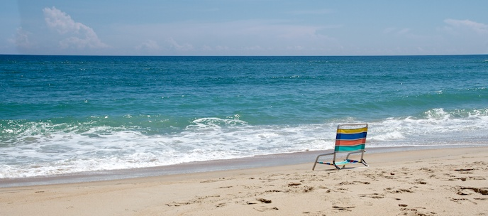 Deep blue waters of the Atlantic Ocean greet the bright tan sands of Cape Hatteras National Seashore where a lone chair waits
