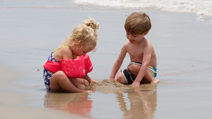 A young girl and boy playing in the sand and surf
